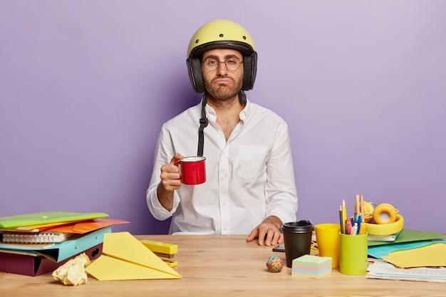 Überarbeiteter mitarbeiter sitzt am schreibtisch