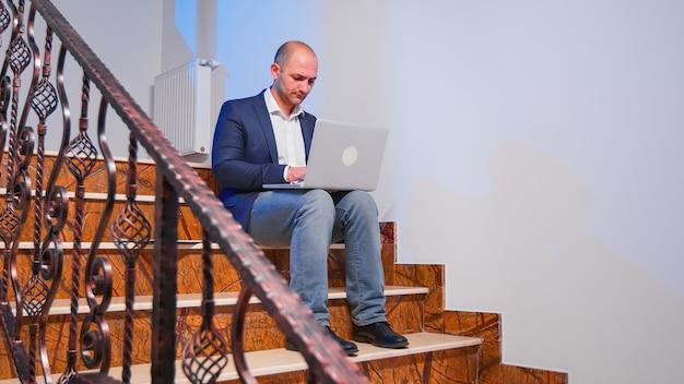 Überarbeiteter müder geschäftsmann am arbeitsplatz, der an der frist für das jobprojekt arbeitet, wobei das notebook im treppenhaus sitzt. selbstbewusster unternehmensunternehmer, der überstunden im geschäftsgebäude mit laptop macht.