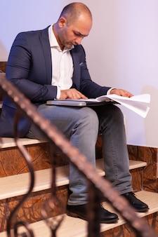 Überarbeiteter müder geschäftsmann, der daran arbeitet, das finanzprojekt vor der frist abzuschließen, die überstunden macht. unternehmer, der spät abends arbeitet, sitzt auf der treppe im baubüro.