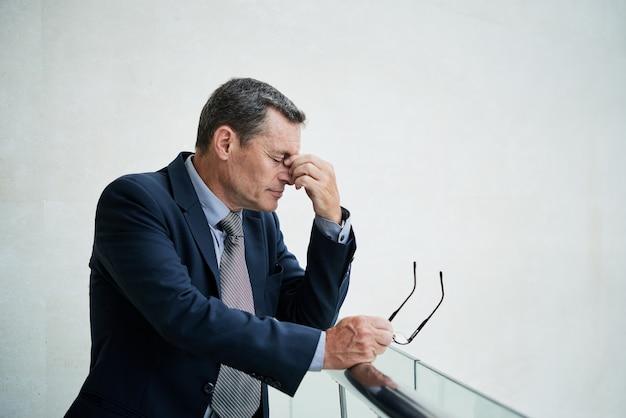 Überarbeiteter reifer mann, der schmerzen verspürt