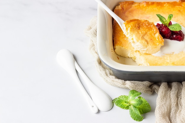 Überbackener pudding mit hüttenkäse, naturjoghurt oder sauerrahm, marmelade mit roten beeren und minze