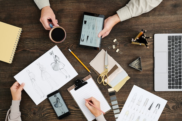 Überblick über die hände des jungen modedesigners mit bleistift über leerem papier in der zwischenablage während der diskussion der neuen kollektion mit dem kollegen