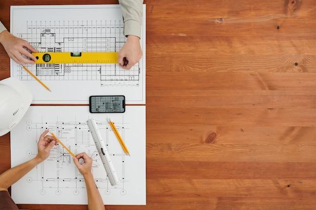 Überblick über die hände zeitgenössischer ingenieure oder bauherren, die am holztisch sitzen und neue skizzen voreinander anfertigen