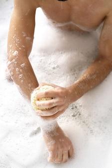Überblick über hemdlosen jungen mann mit schwamm, der seine arme wäscht, während er im bad mit heißem wasser und schaum sitzt