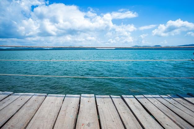 Überbrücken sie hölzerne gehende weise im meer am blauen himmel hut-chao-laostrandes