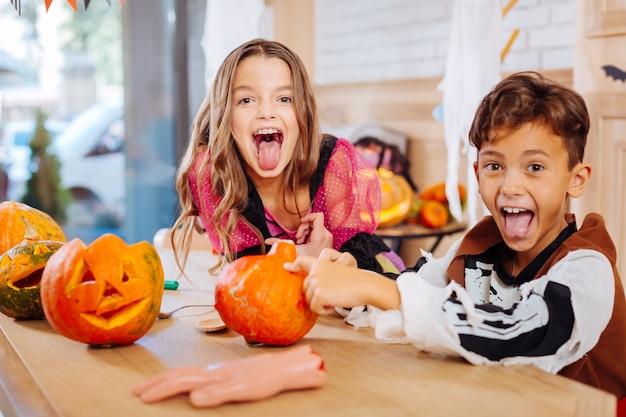 Überemotionale kinder. dunkelhaarige brüder und schwestern in halloween-kostümen fühlen sich übermotiviert