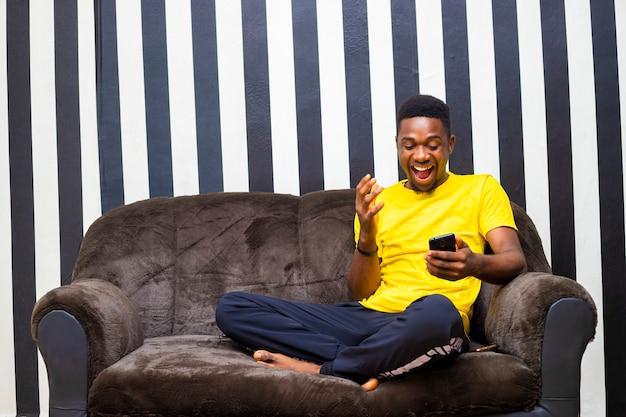 Übererregter junger schwarzafrikanischer männlicher hipster, der feiert, nachdem er gute nachrichten vom handy erhalten hat, die online mit freunden chatten, die in seinem wohnzimmer sitzen