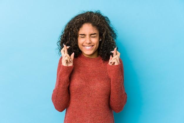 Überfahrtfinger der jungen frau des gelockten haares des afroamerikaners für das haben des glücks