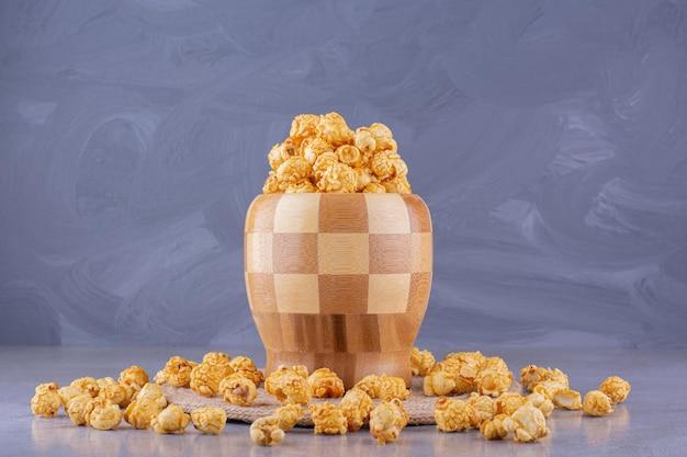 Überfüllte, karierte schüssel, umgeben von verstreutem karamell-popcorn auf marmorhintergrund. foto in hoher qualität
