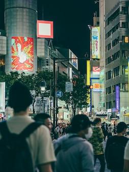 Überfüllte straße in der nacht in der stadt mit menschen