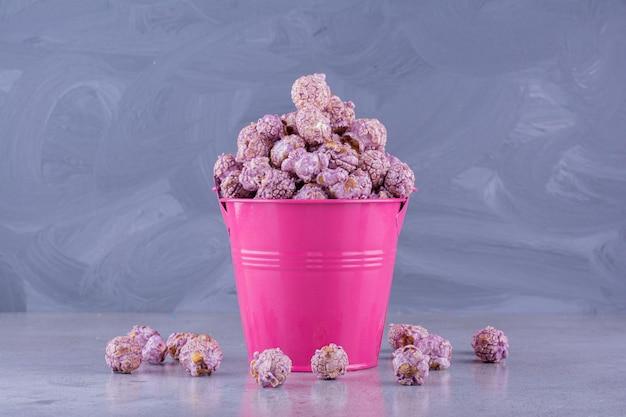 Überfüllter eimer mit aromatisiertem popcorn, das auf marmorhintergrund herausgefallen ist. foto in hoher qualität