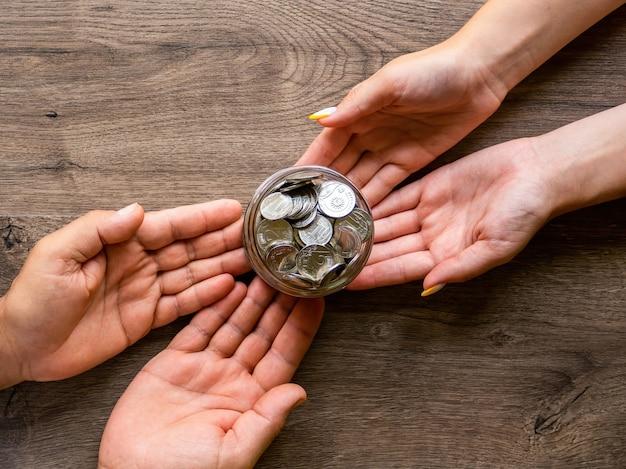 Übergabe der dose mit metallmünzen von mann zu frau