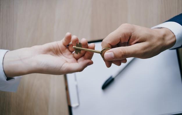 Übergabe des schlüssels von hand zu hand an die arbeitsdokumente für die unternehmensfinanzierung im büro