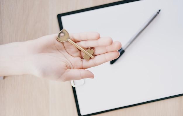 Übergabe des schlüssels von hand zu hand und arbeitsunterlagen für die unternehmensfinanzierung im büro. hochwertiges foto