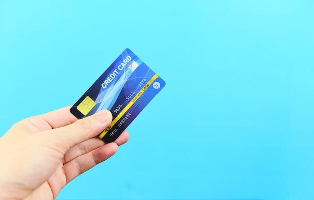 Übergeben sie das halten der kreditkarte auf blauem hintergrund - zahlen sie das on-line-einkaufen, das mit geldbörsenkonzept der kreditkartentechnologie e zahlt