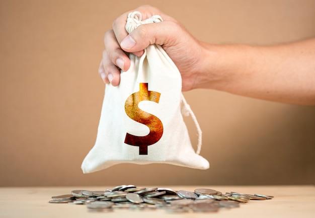 Übergeben sie das halten der us-dollar tasche auf dem haufen des münzenstapelns