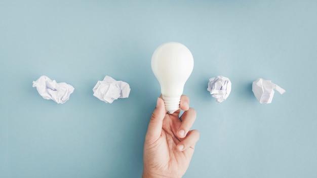 Übergeben sie das halten der weißen glühlampe mit zerknitterten papierbällen auf grauem hintergrund