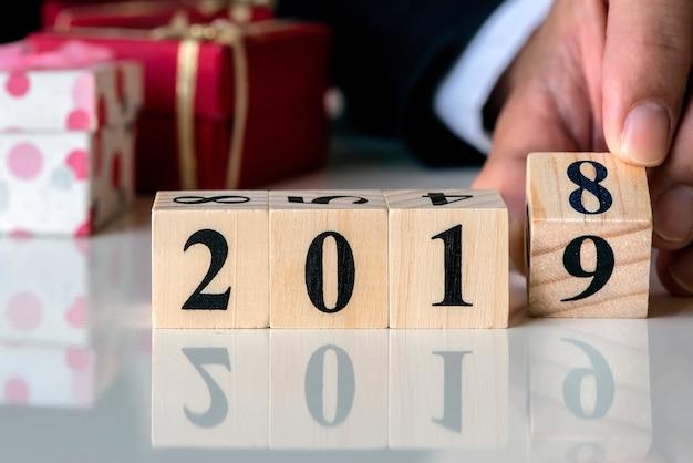 Übergeben sie das halten des hölzernen würfelkalenders mit nr. 2019, konzept des guten rutsch ins neue jahr 2019.