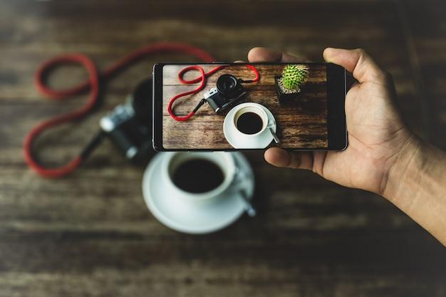 Übergeben sie das halten des intelligenten telefons, das foto des kaffees und der kamera auf holztisch macht.