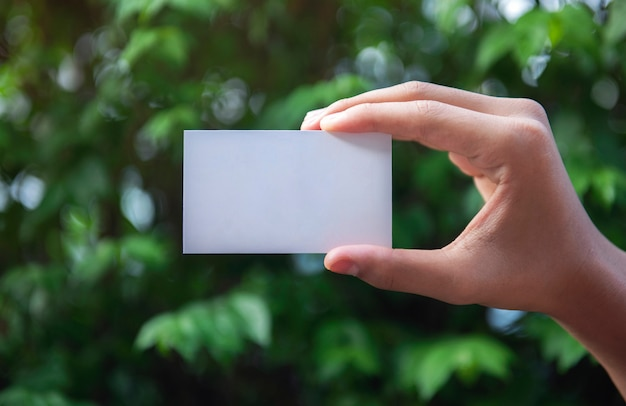 Übergeben sie das halten einer weißen visitenkarte leerer text auf naturhintergrund