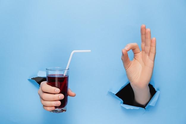 Übergeben sie das halten eines glases frischen roten safts mit einem stroh durch heftige wand des blauen papiers.