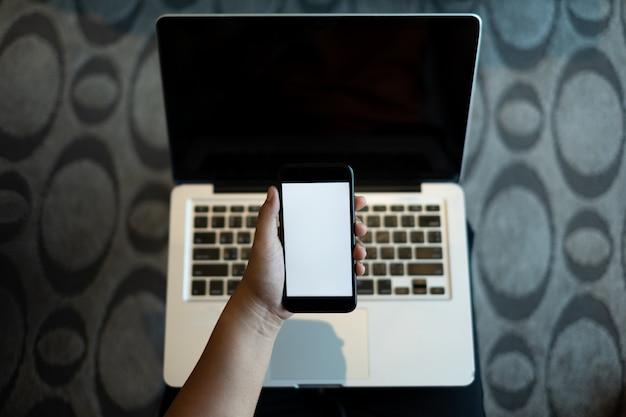 Übergeben sie das halten eines handys mit weißem leerem bildschirm über dem laptop