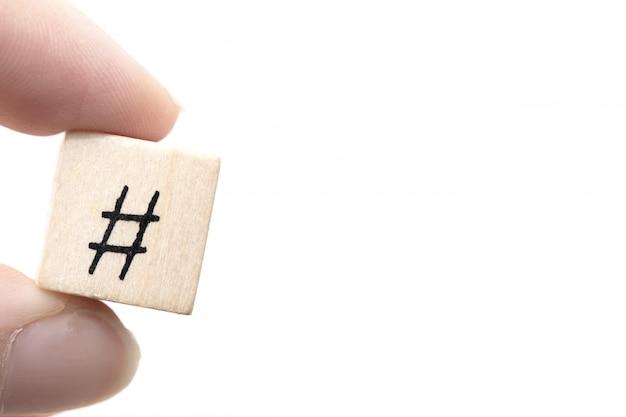 Übergeben sie das halten eines hölzernen würfels mit einem hashtag ein symbol, social media-konzept
