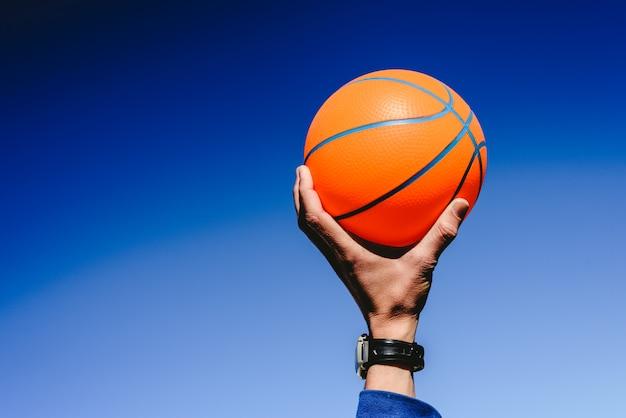 Übergeben sie das halten eines orange basketballballs auf hintergrund des blauen himmels