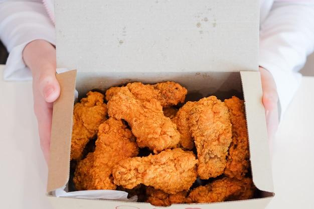 Übergeben sie das halten von köstlichen knusperigen gebratenen hühnertrommelstöcken u. -flügeln für snack.
