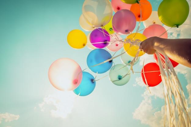 Übergeben sie das halten von multi farbigen ballonen, die mit einem retro- weinlese instagram filtereffekt erfolgt sind.