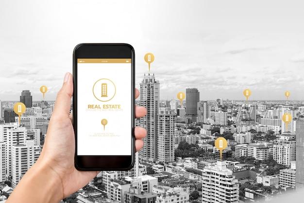 Übergeben sie das halten von smartphone mit anwendung, um immobilien auf bildschirm zu finden
