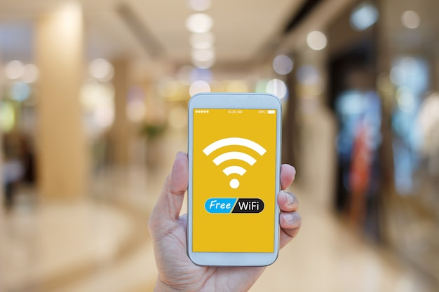 Übergeben sie das halten von smartphone mit freiem wifi auf dem schirm vorbei, der im einkaufszentrumhintergrund verwischt wird