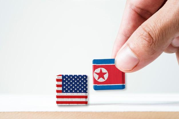 Übergeben sie das setzen der hölzernen kubikflagge des bildschirms nordkorea und der usa-flagge. es ist symbol des konflikts für beide länder in der militär- und wirtschaftssanktion der atomwaffe