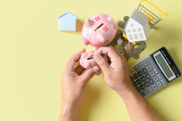 Übergeben sie das setzen der münze zum sparschwein und geldkonzept sparen