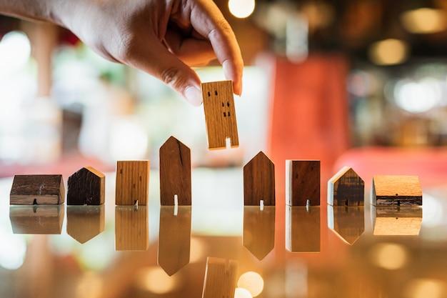 Übergeben sie das wählen des miniholzhausmodells vom modell und von der reihe des münzengeldes auf hölzerner tabelle