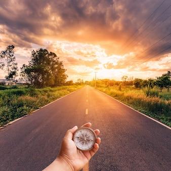 Übergeben sie den mann, der kompass auf straße mit himmelsonnenuntergang hält.