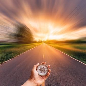 Übergeben sie den mann, der kompass auf unscharfer straße mit himmelsonnenuntergang hält.