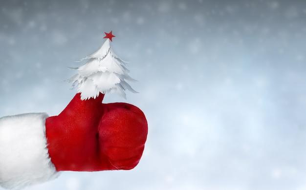 Übergeben sie den roten fäustling des weihnachtsmanns, der wie zeichen mit kleinem papierweihnachtsbaum auf dem daumen zeigt