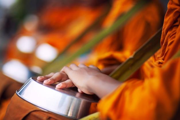 Übergeben sie den thailändischen buddhistischen mönch, der wartet, um morgenessenangebot zu erhalten