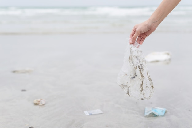 Übergeben sie die frau, die die plastiktaschereinigung auf dem strand aufhebt