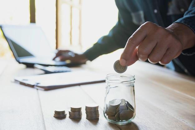 Übergeben sie eine münze mit dem geldmünzenstapel, der für geschäft wächst