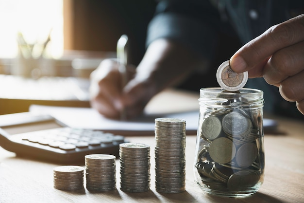 Übergeben sie eine münze mit dem geldmünzenstapel, der für geschäft wächst.