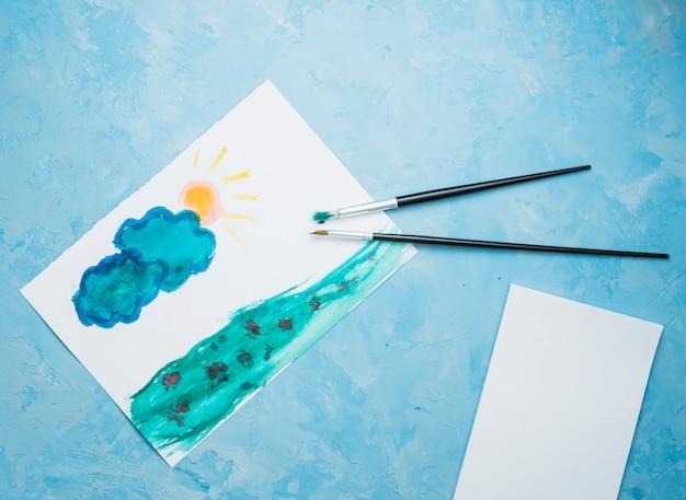 Übergeben sie gezogene zeichnung auf weißbuch mit malerpinsel über blauem hintergrund
