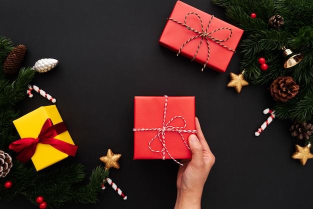 Übergeben sie griffweihnachtsgeschenkbox mit kiefer- und weihnachtsdekoration auf schwarzem hintergrund