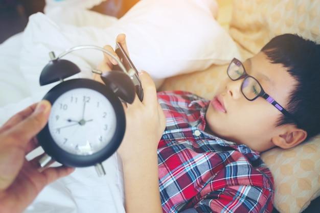 Übergeben sie sich heraus zeigen für wecker am morgen, der junge, der spiel am faulen liegenden telefon spielt