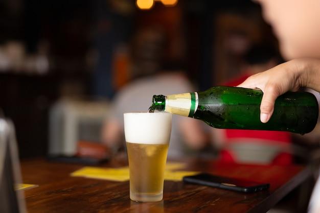 Übergeben sie strömendes bier von der flasche in ein glas im unschärfehintergrund.