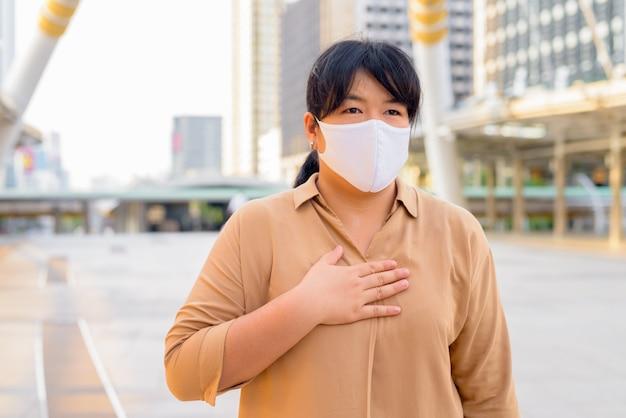 Übergewichtige asiatische frau, die maske mit hand auf brust in der stadt trägt