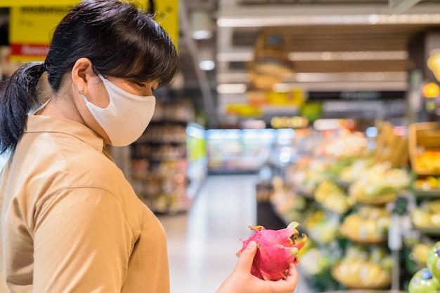 Übergewichtige asiatische frau mit maske zum schutz vor dem ausbruch des koronavirus im supermarkt