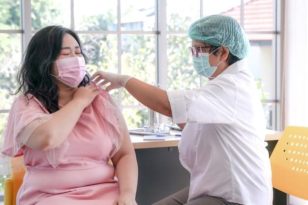 Übergewichtige asiatische patientin, die ihren arm zur injektionsimpfung gegen covid 19 krankenschwester gibt