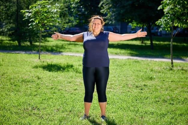 Übergewichtige europäische frau macht morgengymnastik in der natur